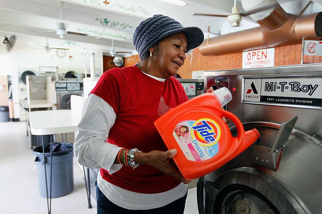 woman putting detergent into washing machine